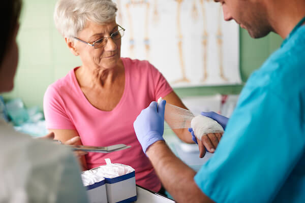Apotheco wound care - nurse wrapping older woman's wrist with medical wrap